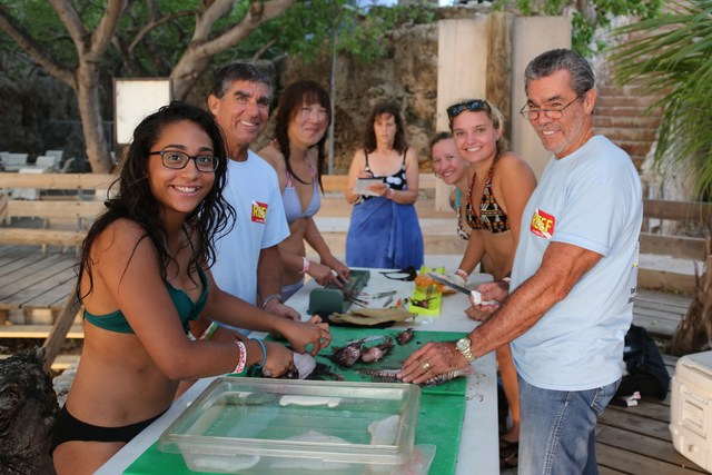 Dissection group: Trip participants smile for a group photo around the dissection table. There was an assembly line: three people measured the lengths, one recorded results, and three filleted the fish for tomorrow's dinner.
