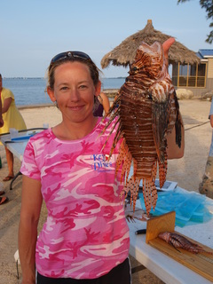 Volunteer Jen Russell holds an invasive lionfish captured during a lionfish derby in South Florida.