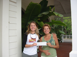 REEF Executive Director Leda Cunningham accepts a check from events volunteer Evelyn McGlone.: Photo by REEF.